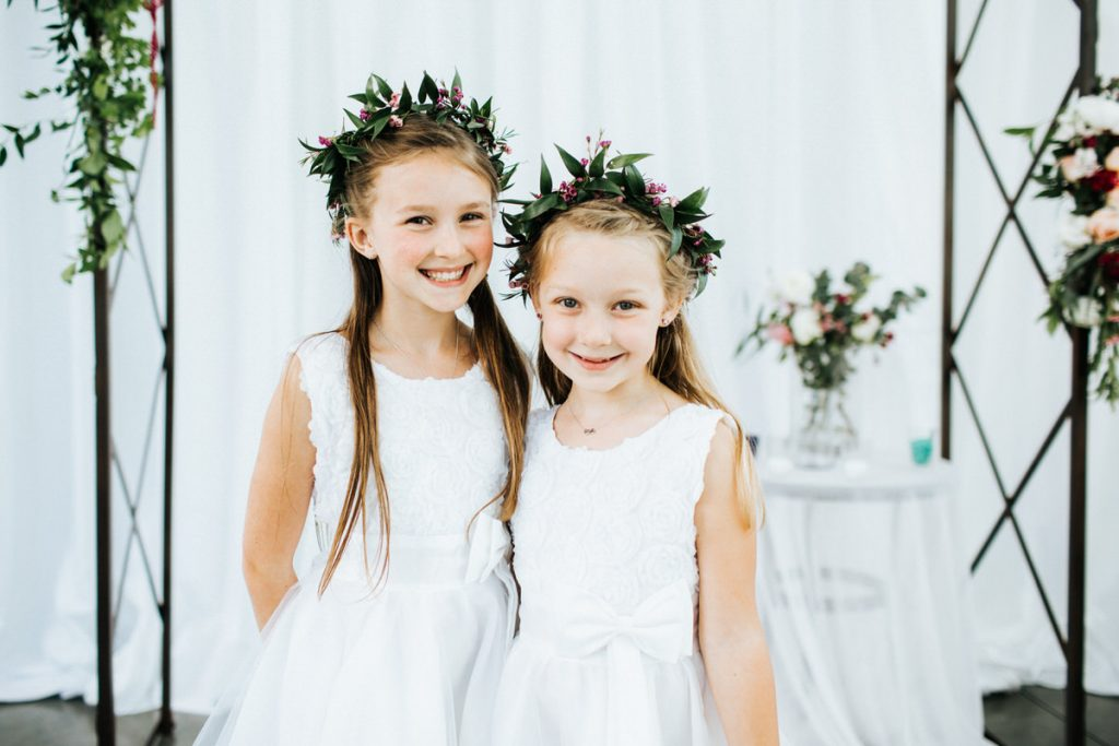 Two girls with flower crowns pose for a picture.
