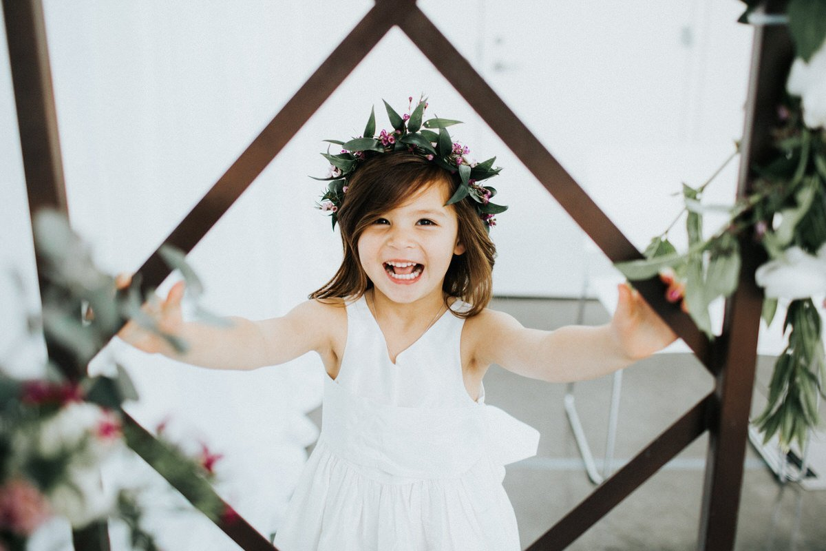 A flower girl laughs while getting her picture taken.