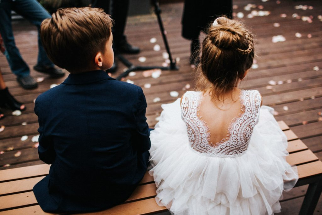 Two kids sit and watch a wedding ceremony at Within Sodo in Seattle
