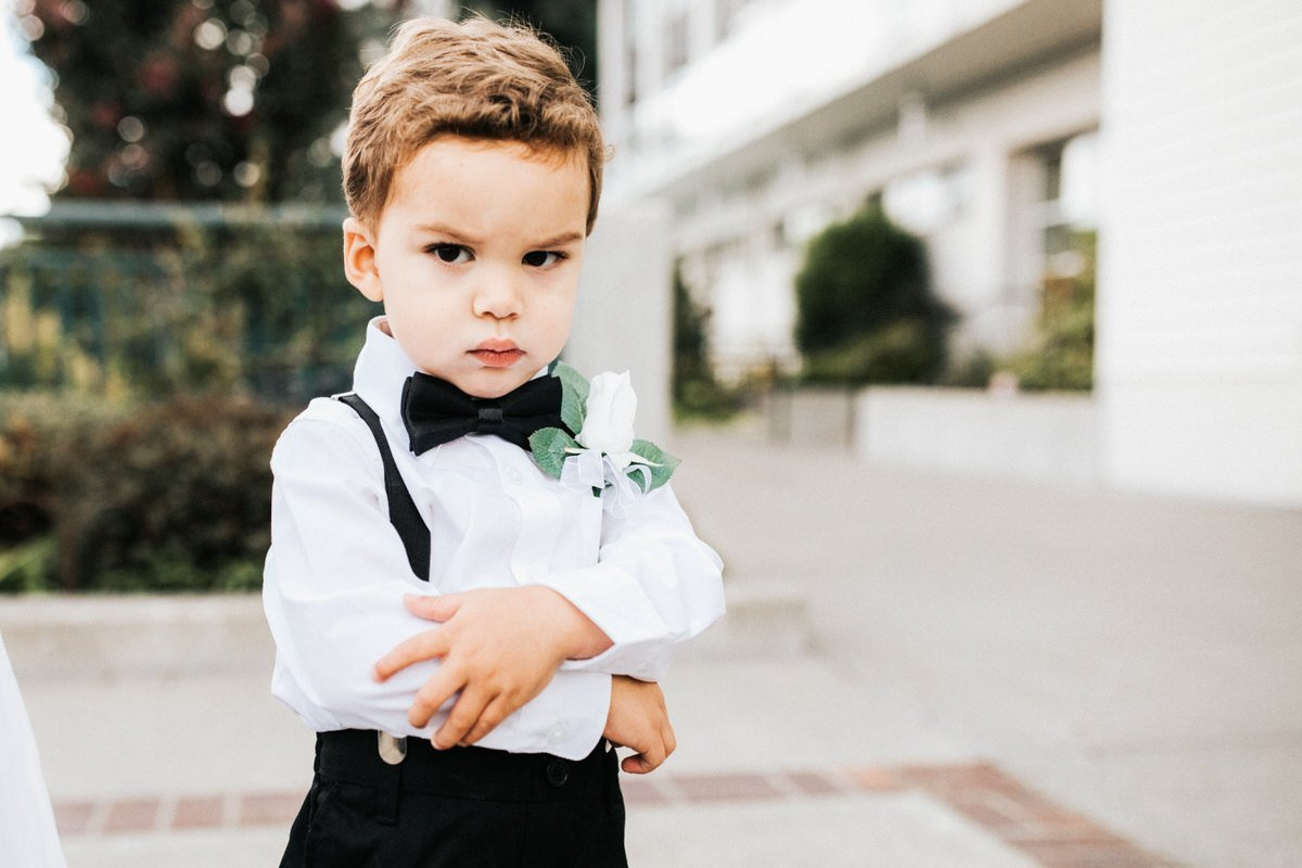 A ring bearer isn't happy to have his picture taken and folds his arms.