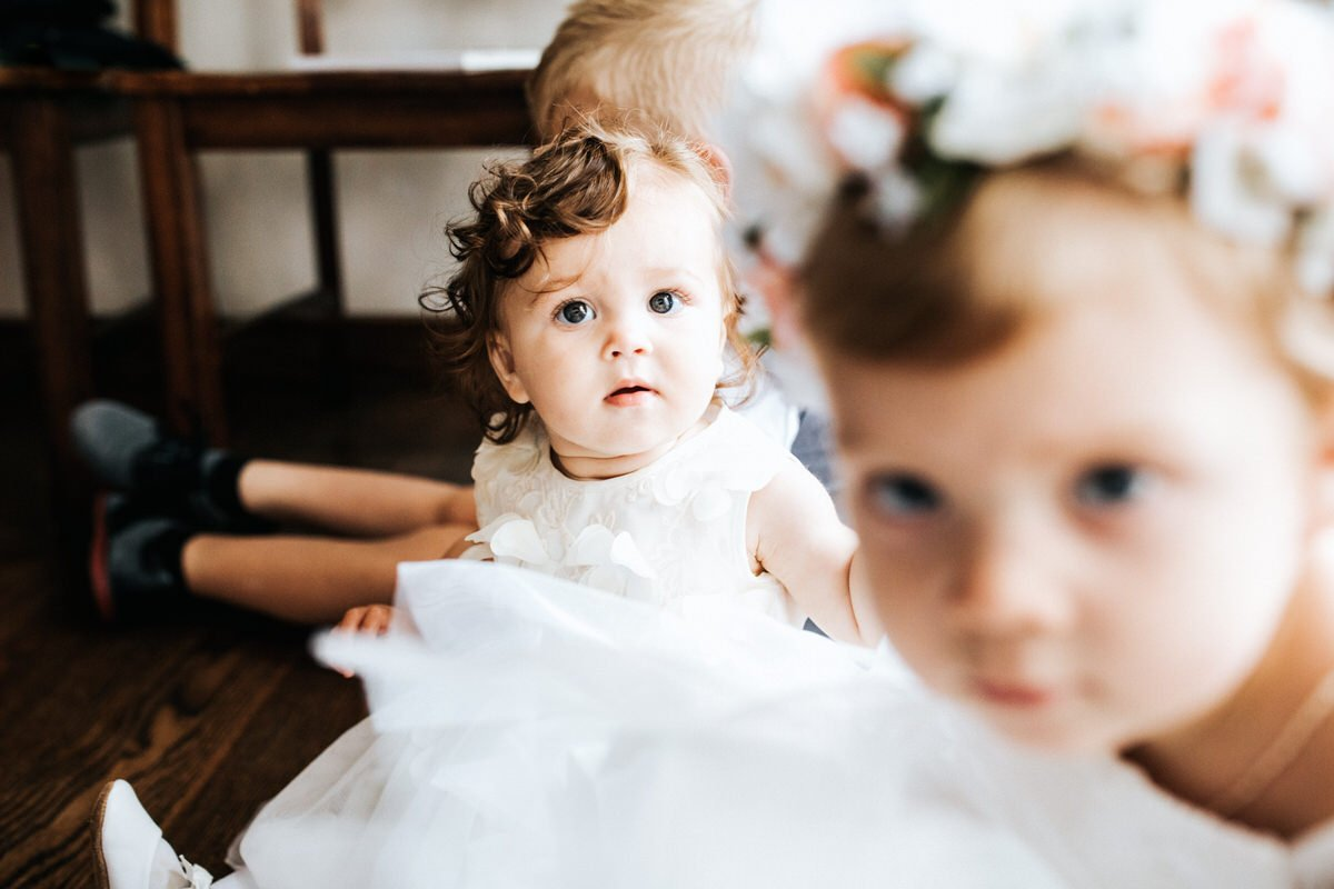 A baby smiles at the camera at a wedding at Chateau Lill in Woodinville.