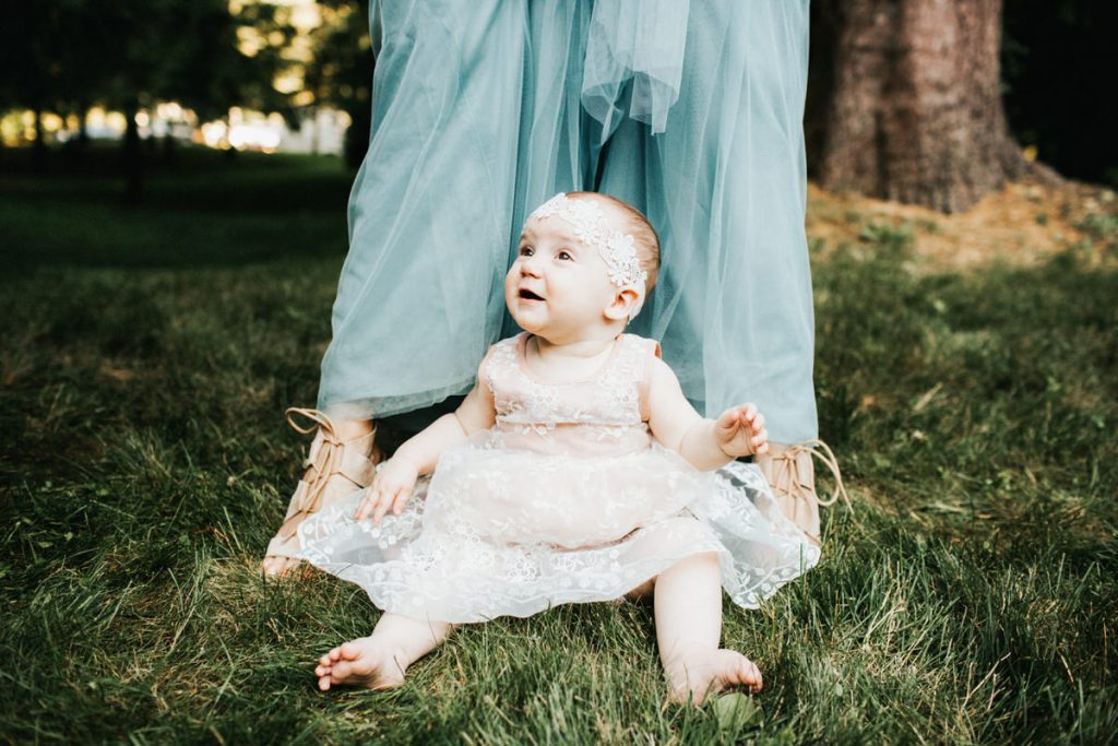A little baby and a bridesmaid pose for a picture.