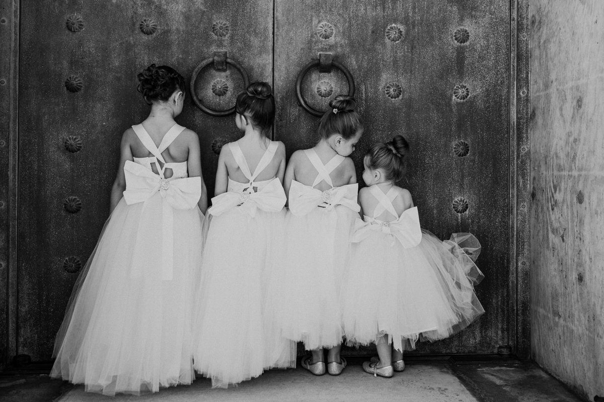 Flower girls line up in front of a door at a wedding in San Francisco.