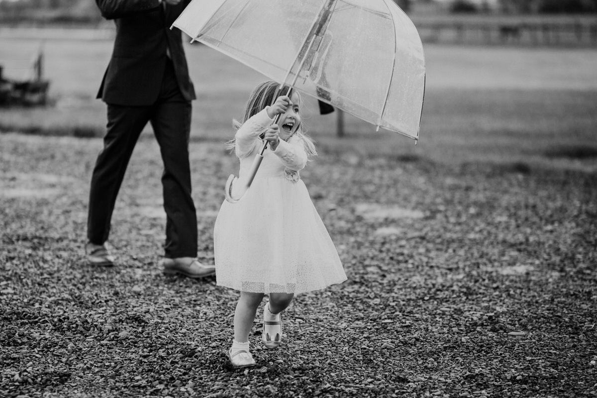 A young girl runs with an umbrella outside in the rain.