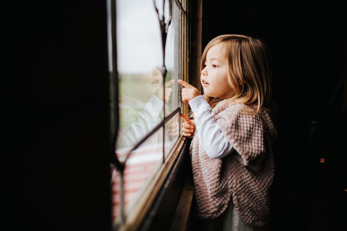 A little girl looks out the window at some horses.