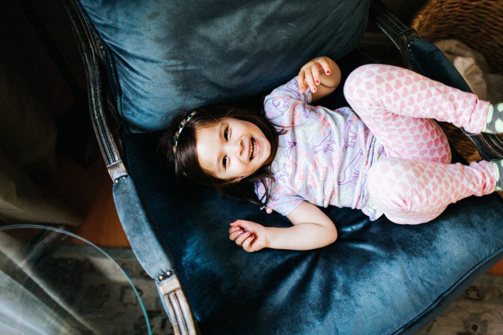 A flower girl laughs while sitting on the couch.