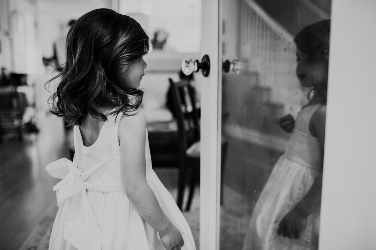 A flower girl looks at herself in the mirror as she gets ready for a wedding in Seattle.