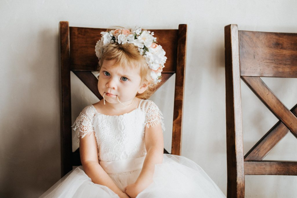 A flower girl with a flower crown looks at the camera.