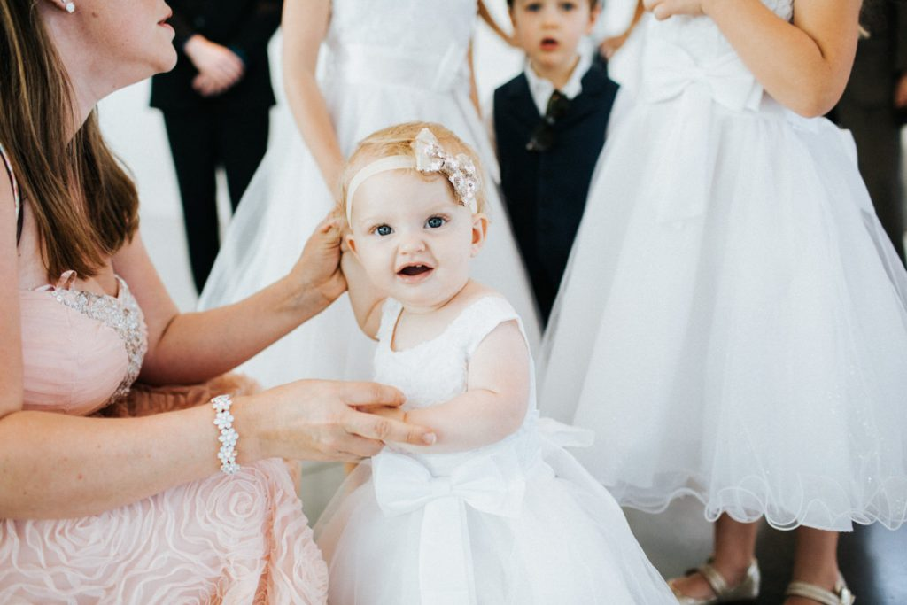 A little baby and her mom get ready for dancing at a wedding.