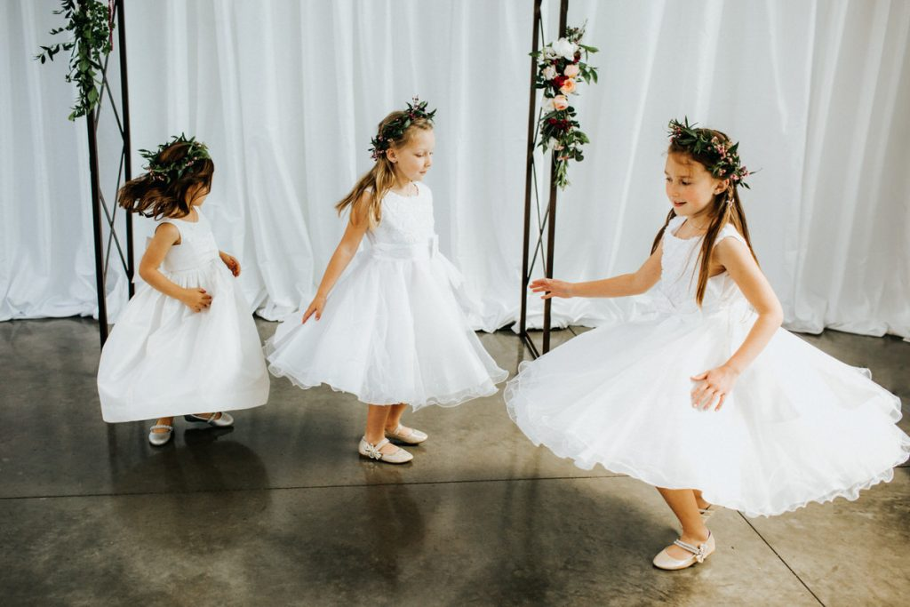 Three girls spin to make their dresses twirl.