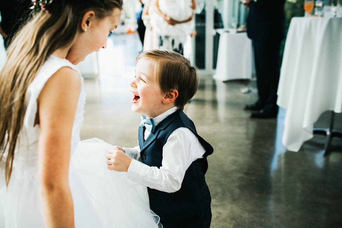 A young kid laughs with his sister.