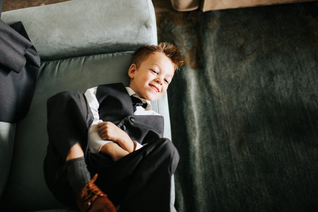 A ring bearer laughs with the groomsmen at a Lake Chelan wedding