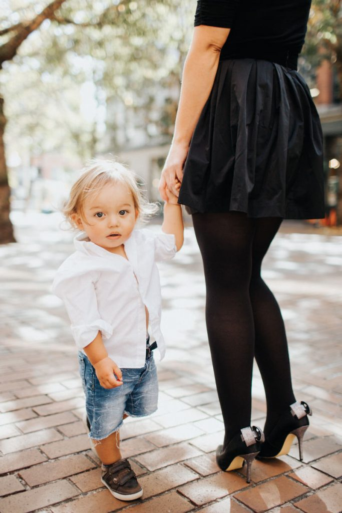A young kid poses with his mom in Pioneer Square Seattle.