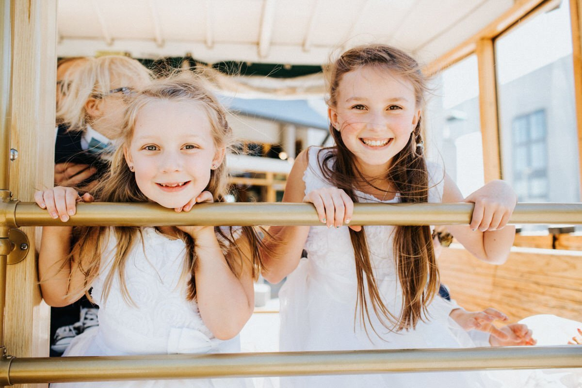 Two sisters laugh and smile at the camera while riding a trolly in Seattle.
