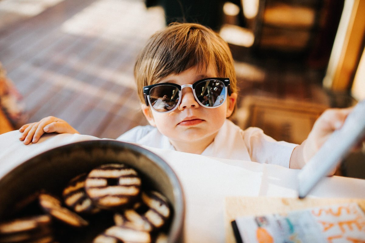 A young kid wears sunglasses and smiles at the camera.