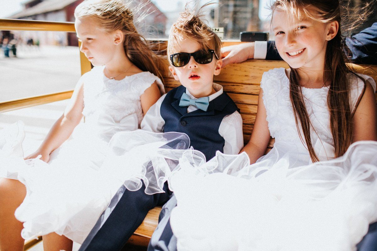 A ring bearer and two flower girls ride a trolly on a sunny day in Seattle.