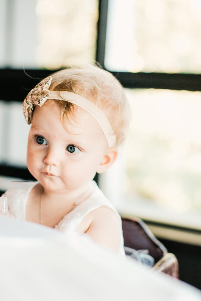 A little baby sits at the table during a wedding at Canlis restaurant in Seattle.
