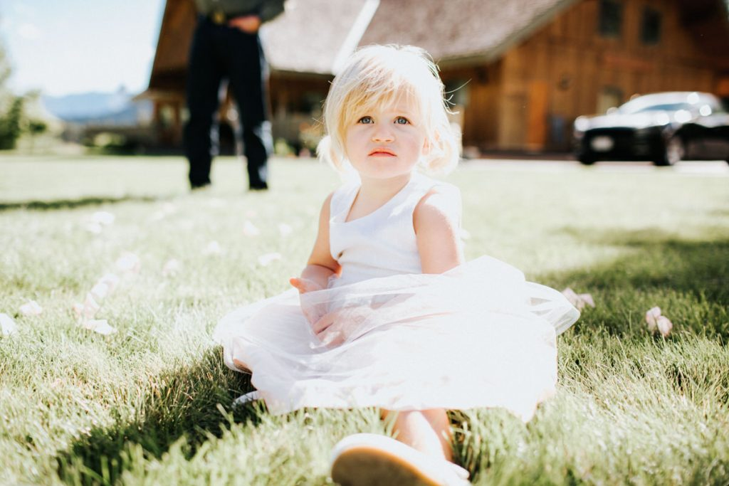 A girl in a pink dress sits in the grass at a wedding at Mountain Springs Lodge.