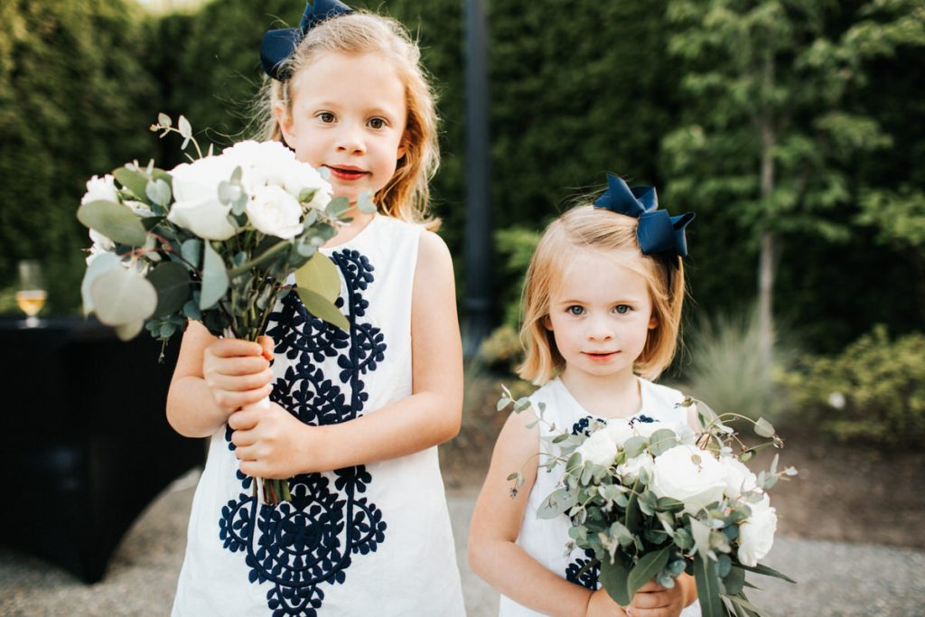 Two flower girls hold the flowers at a wedding at the Columbia Winery in Woodinville.