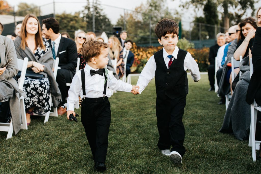 Two kids hold hands while walking down the aisle at the Seattle Tennis Club