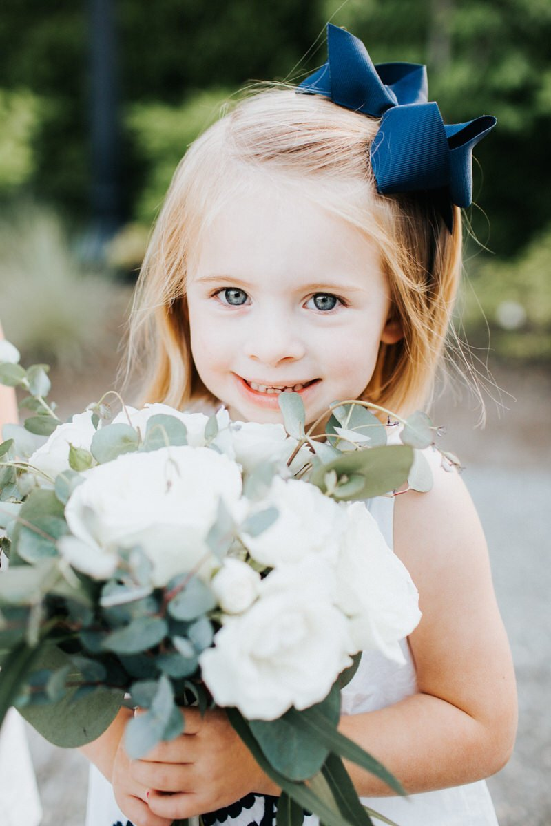 A girl holds flowers at a wedding at the Columbia Winery in Woodinville.