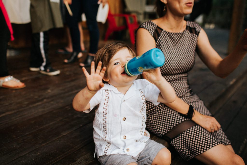 A kid waves at the camera as he hangs out with his parents at a wedding in Leavenworth.