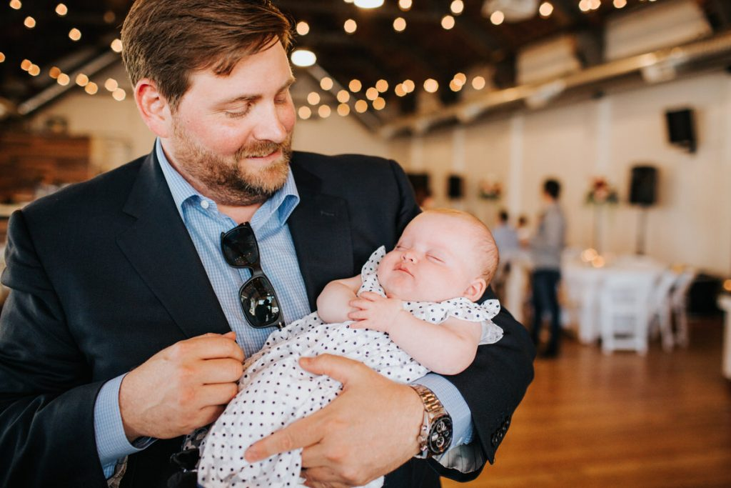 A dad holds his baby at a reception at Metropolist in Seattle.