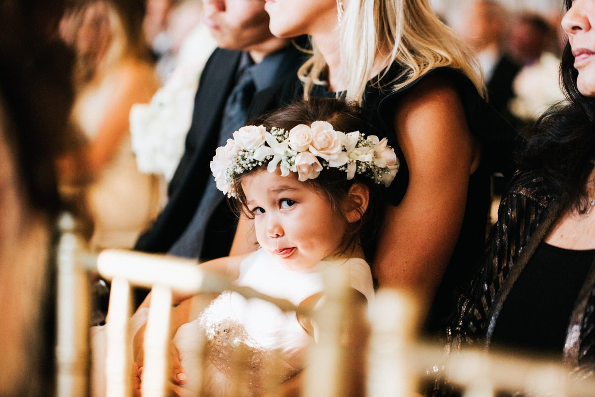 A flower girl sits during the ceremony at a wedding at the Four Seasons Hotel in Seattle.