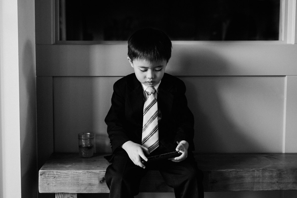 A kid dressed up in a suit plays on his phone.