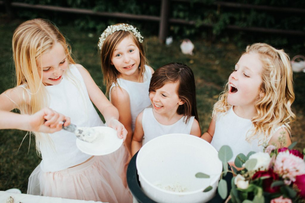 A group of flower girls laughs together while scooping ice cream at a wedding in Mountain Springs Lodge in Leavenworth.