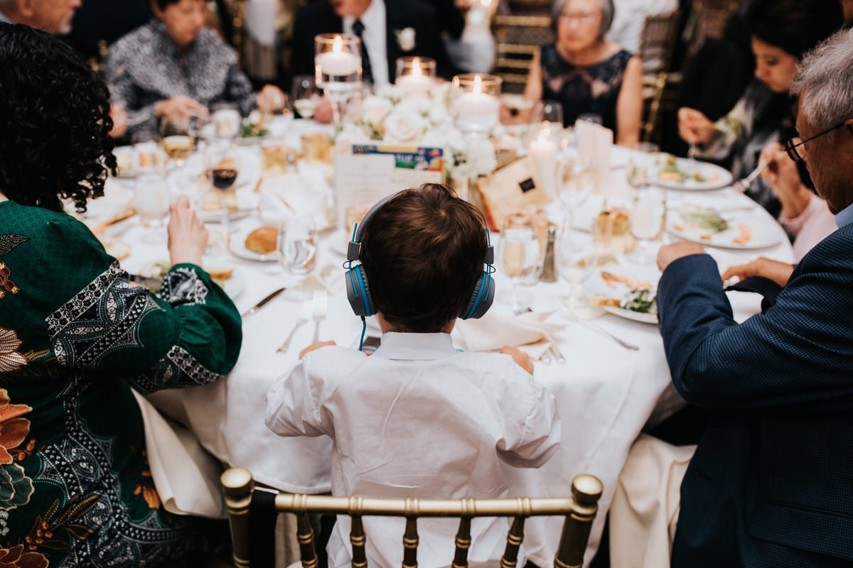 A kid sits during a reception at the four seasons hotel in Seattle with his headphones on.