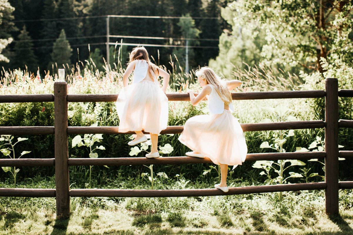 Two flower girls climb a fence and have fun at Mountain Springs Lodge.