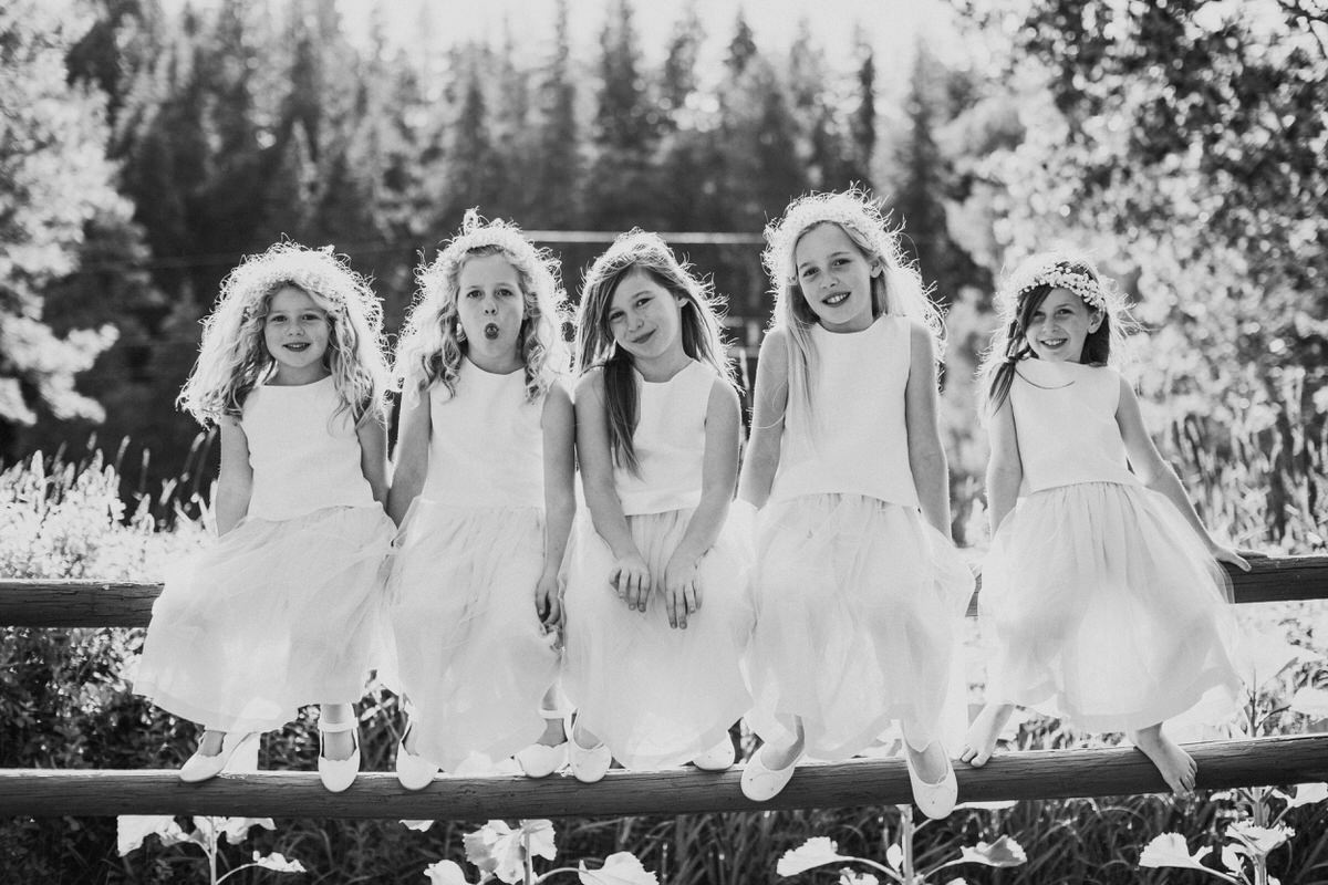 Five flower girls sit on a fence at a rustic wedding in Mountain Springs Lodge in Leavenworth.
