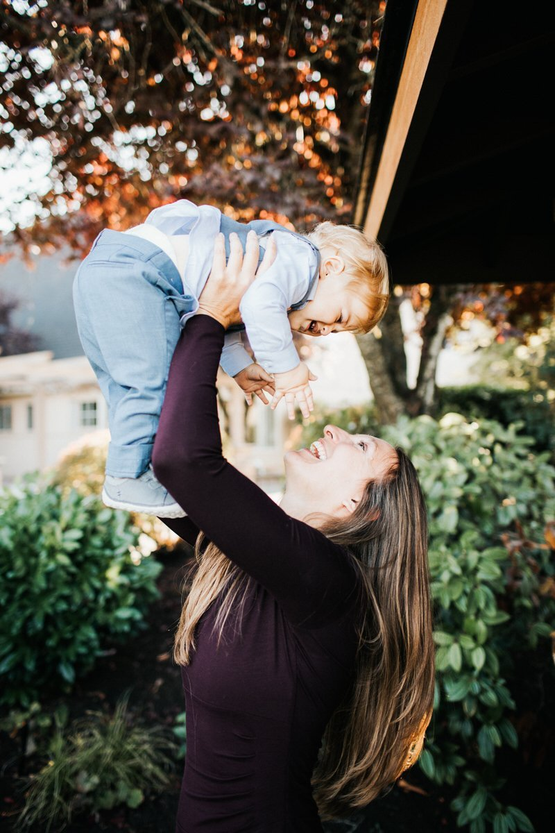 A mom holds her baby up and plays with him.