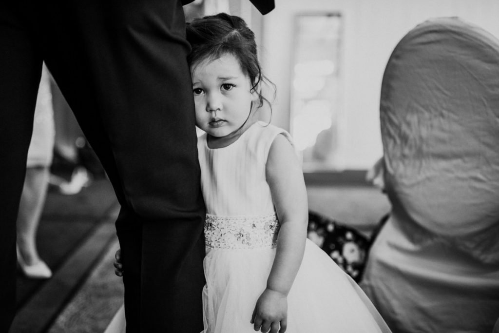 A shy flower girl hides behind her dad at a Four Seasons Hotel wedding in Seattle.