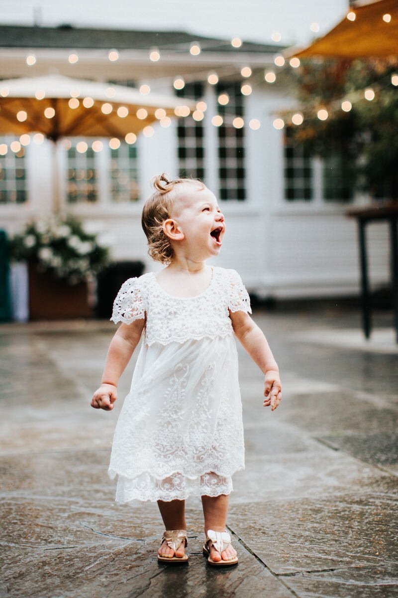 A young girl laughs in the rain at a wedding in Roche Harbor Resort.