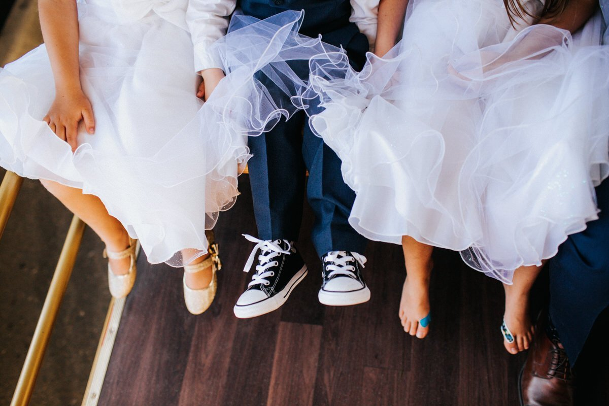 A photo of three pairs of shoes on young kids.