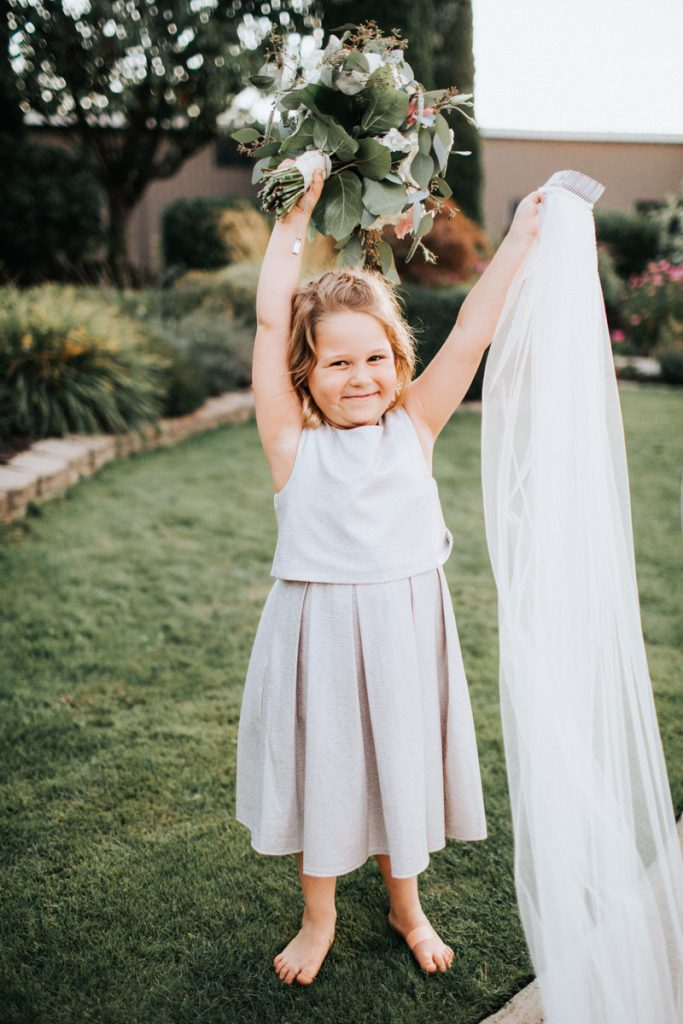 An excited flower girl holds the veil.