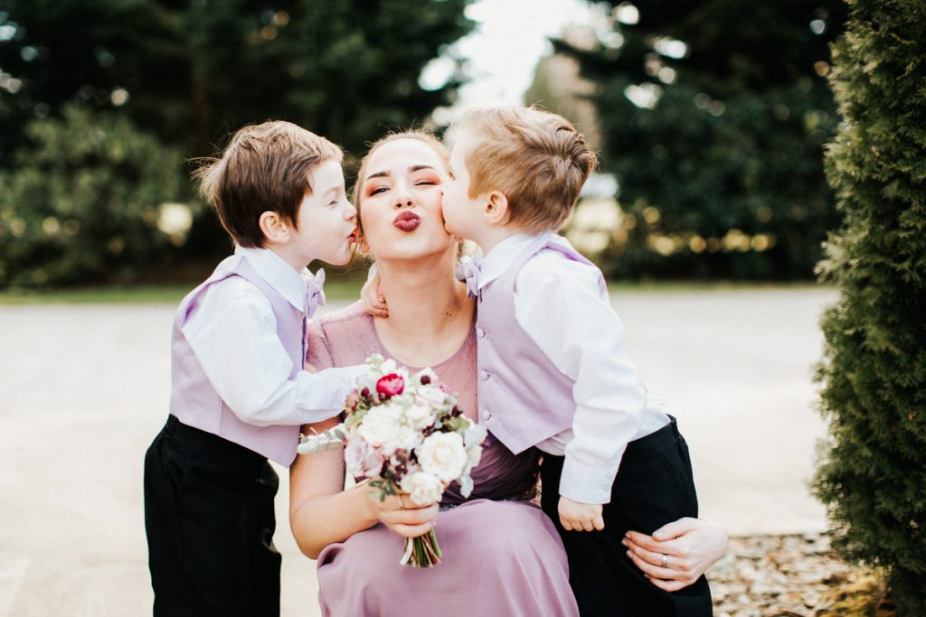 Two ring bearers kiss a bridesmaid during a wedding in Woodinville.