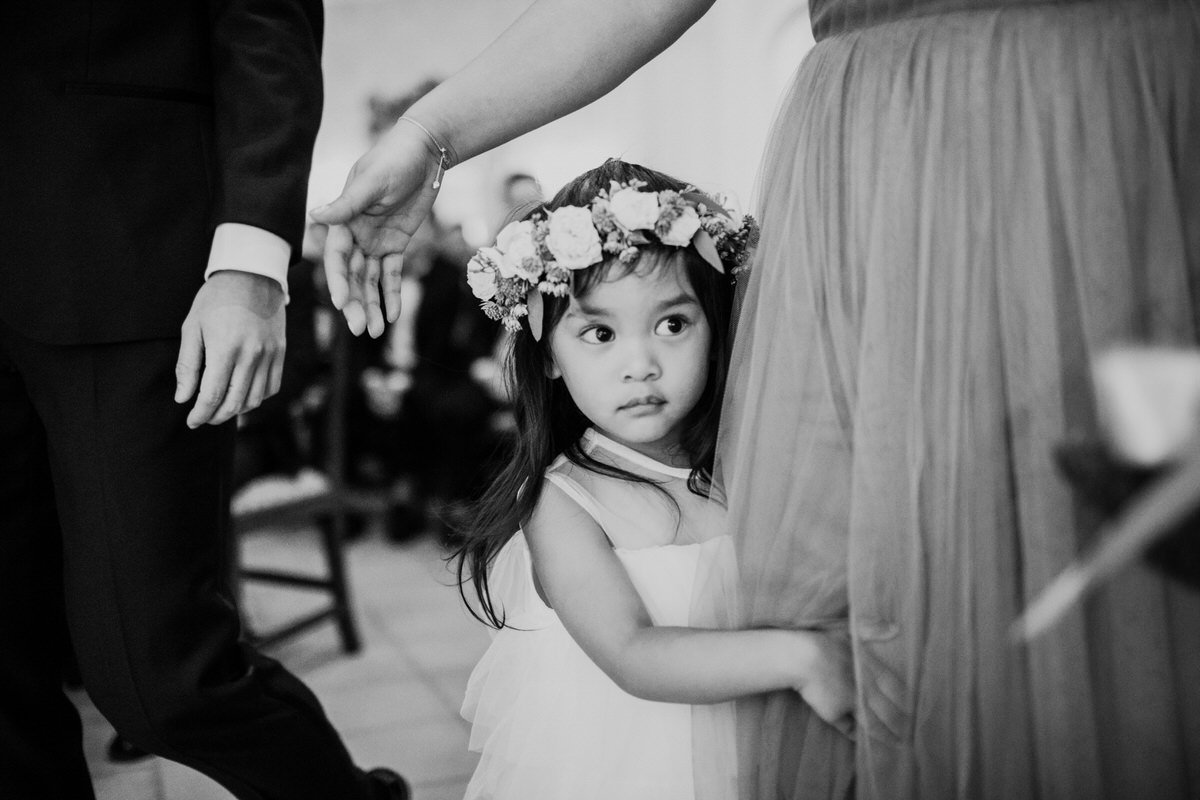 A flower girl hides behind her mom as they walk down the aisle at a wedding in Seattle.