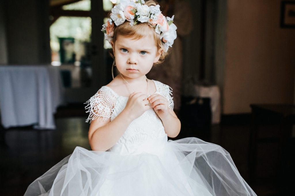 A flower girl stares at the camera at a wedding at Chateau Lill in Woodinville.