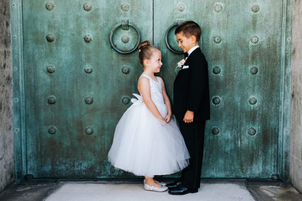 During a wedding in San Francisco a shy flower girl and ring bearer look at each other.
