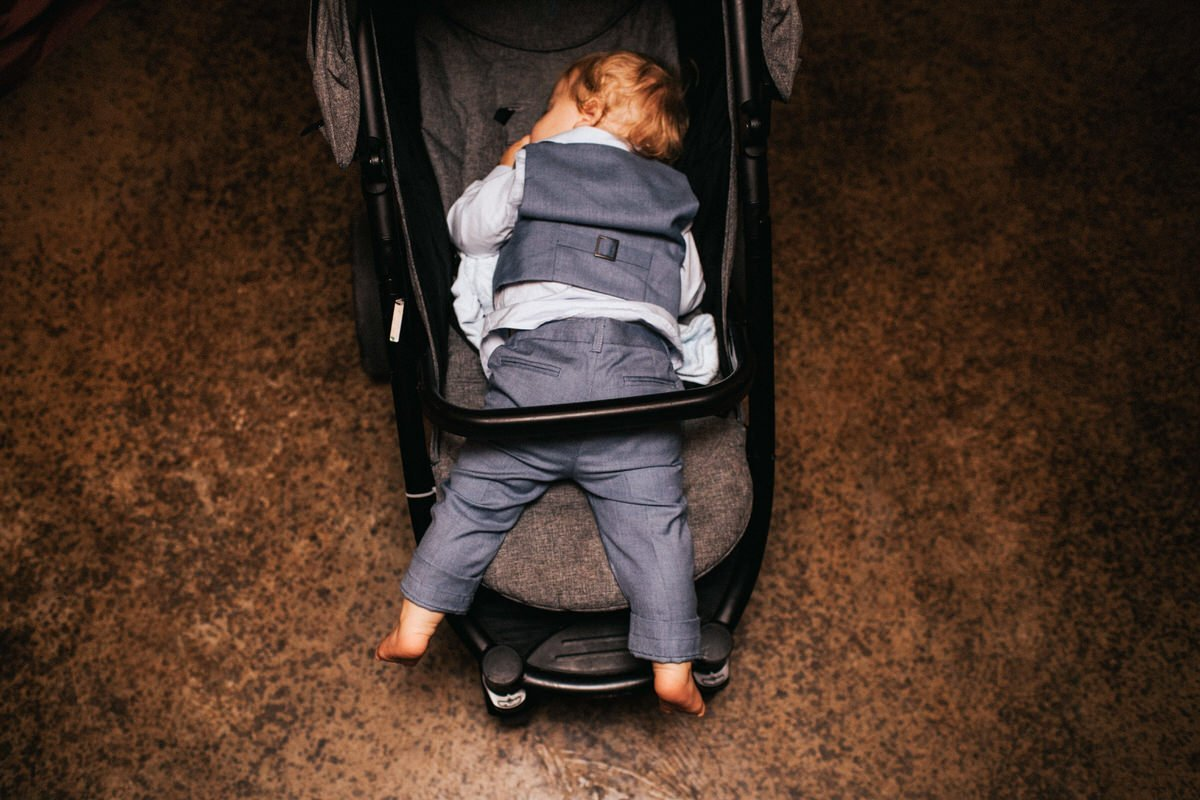 After a long day, a kid passes out in his stroller at a wedding in Snohomish.
