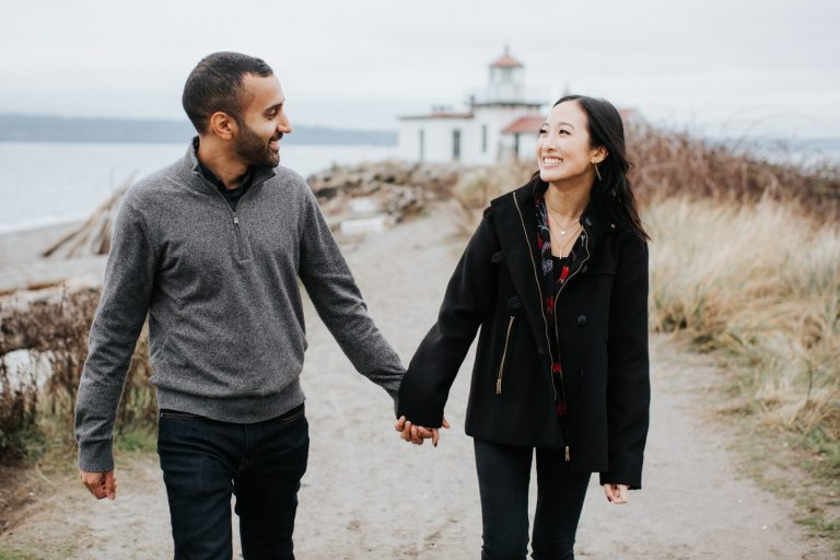 A couple walks and laughs during their engagement session at discovery park